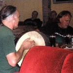 Ernine playing bodhrán in local pub's traditional music session