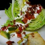 Classic wedge of iceberg lettuce with housemade green goddess dressing, avocado, bacon, and toma