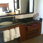 sink area across from beds- stool and shower in separate room.