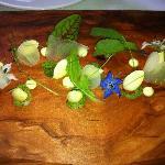 crispy shrimp, eucalyptus puree served on a polished wood tray with wildflowers