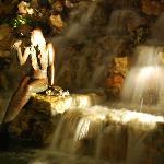 Bronze mermaid statue in the waterfall