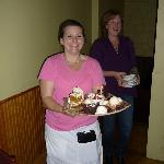 Server Sheila (left) and Lisa Ayllon bring in a birthday dessert platter.