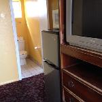 large tv, fridge/freezer, microwave (bathroom behind appliances)