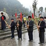 Miao villagers playing instruments as tourists leave in the late afternoon