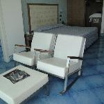 White leather rocking chairs and ottoman in front of window