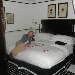 Nuestro cuarto con una botella de champagne y pétalos en la cama