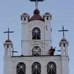 guy playing guitar on top of the church