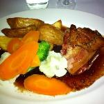 deliscious lamb slow roasted with bacon, crisp potatoes steamed veges in red currant sauce