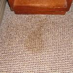 Coffee (?) stain on floor in front of nightstand.