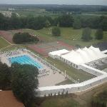 View of outdoor pool, tennis courts and event tent.