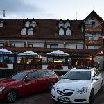 Ansicht von Parkplatz + Hotel von Strasse her
