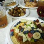 Belgium Waffle with fresh fruit, hash browns, Cinnamon roll and French Toast