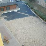 Sandy lot with volleyball net on east side of hotel.