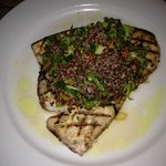 Swordfish steak topped with a warm salad consisting of quinoa, grape tomatoes, arugula, cucumber