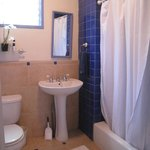 Tiled bathroom w/ shower & tub shared by guests in the 2 bedroom Sugar Shack