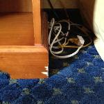 Chipped end-table with wire bundle, beside bed.