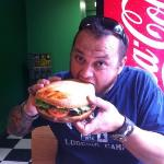 """my husband attempting the giant black bean burger called """"The Jen Burger"""""""