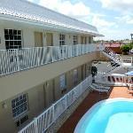 Bloque sur del hotel con primer y segundo piso y vista de la piscina desde la terraza.