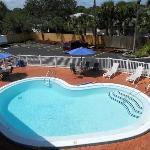 Piscina del hotel mirada desde la terraza con quitasoles azules.