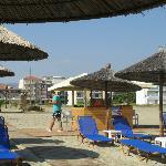 Zandstrand met parasols met op de achtergrond het hotel