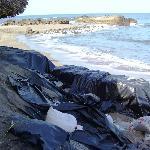 weg naar het strand langs plastic zakken die het wegspoelen van het terras moeten tegenhouden