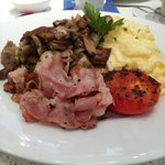 Grillied pancetta with scrambled egg, mushrooms and tomato on Italian bread