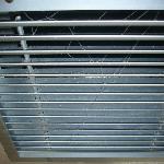 Toiles d'araignées dans la grille de la climatisation.