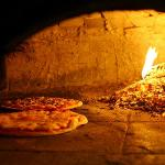 Thin crust pizza baking in wood fired oven