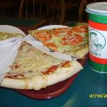 4 cheese, pesto tomato, cheese pizza and drink in the dining area.