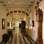 A hall in the museum full of paintings, furniture and clocks