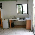 Small kitchen in room with 2 burner stove, sink & mini fridge.