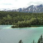 Green lake with mountain backdrop