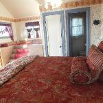 The bed, bathroom door and elevated, deep, Jacuzzi bathtub