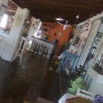 Área social com recepção, ambiente para leitura e o bar ao fundo