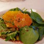 Spinach salad with orange slice and pistachios