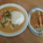 Panang drowning in milky red curry sauce and chicken satay