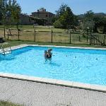 la piscina con sullo sfondo appartamenti e casale