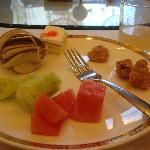 A breakfast of popcorn chicken, hanoi?, cake, watermelon, and cucumbers.