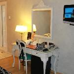 tiene un mobiliario precioso, aquí: la tv, escritorio y se asoma el pasillo hacia la puerta.