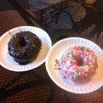 Cake donut with chocolate icing and chocolate sprinkles, and strawberry icing/rainbow sprinkles