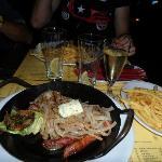Piatto di carni miste con cipolle, zucchine, burro alle erbe e patatine fritte