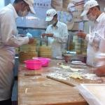 Rollers meticulously at work wrapping the famous dumplings.