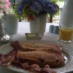 Delicious breakfast (cinnamon raisin french toast, bacon, freshly squeezed OJ, coffee, and peach