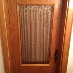 door to the room, part glass with a curtain ??