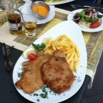 Wienerschnitzel with fries served in the patio.