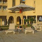Parecchie sdraio con ombrellone a lato piscine