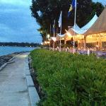 Waterfront wedding reception with lights from the tents.