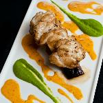 Monkfish with smoked pork belly, pea puree and chorizo cream sauce