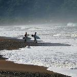 Surfers in early morning entering ocean near hotel - Jaco Beach