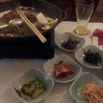 Tischgrill auf koreanisch mit Fleisch und vielen kleinen Extras
